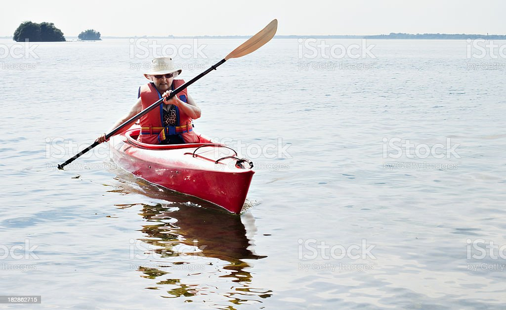 Senior woman paddling in red canoe royalty-free stock photo