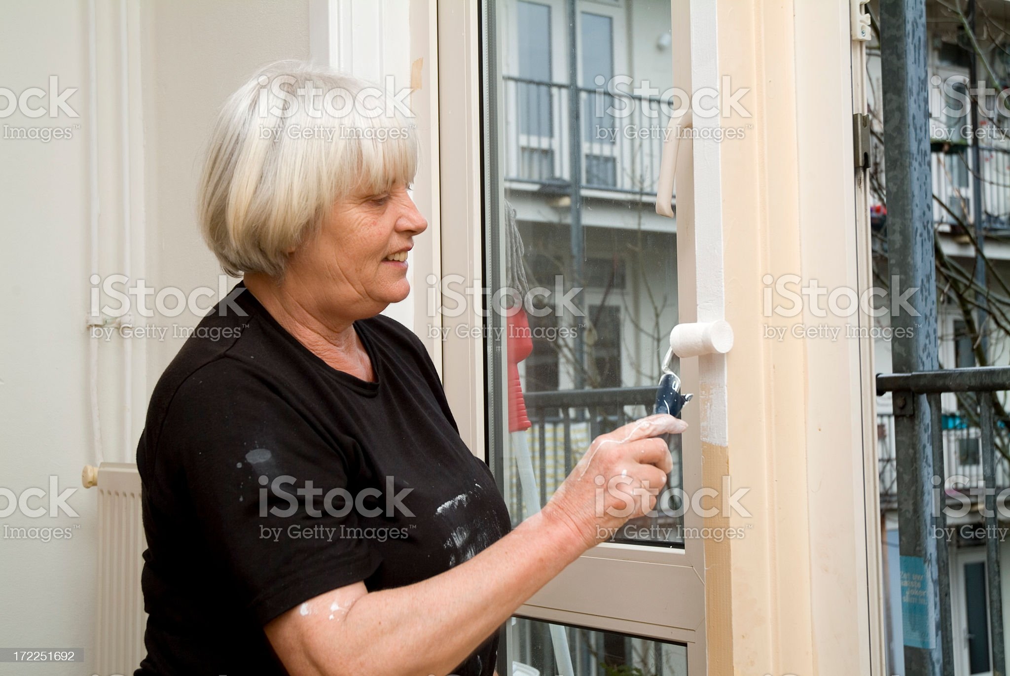 Senior woman painting a door 2 royalty-free stock photo