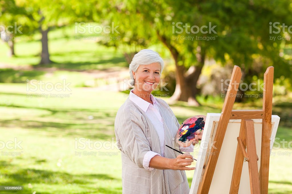 Senior woman painting in the park royalty-free stock photo