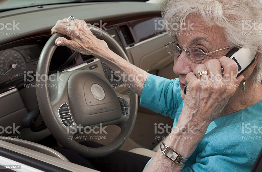 senior woman parked in car talking on cell phone stock photo