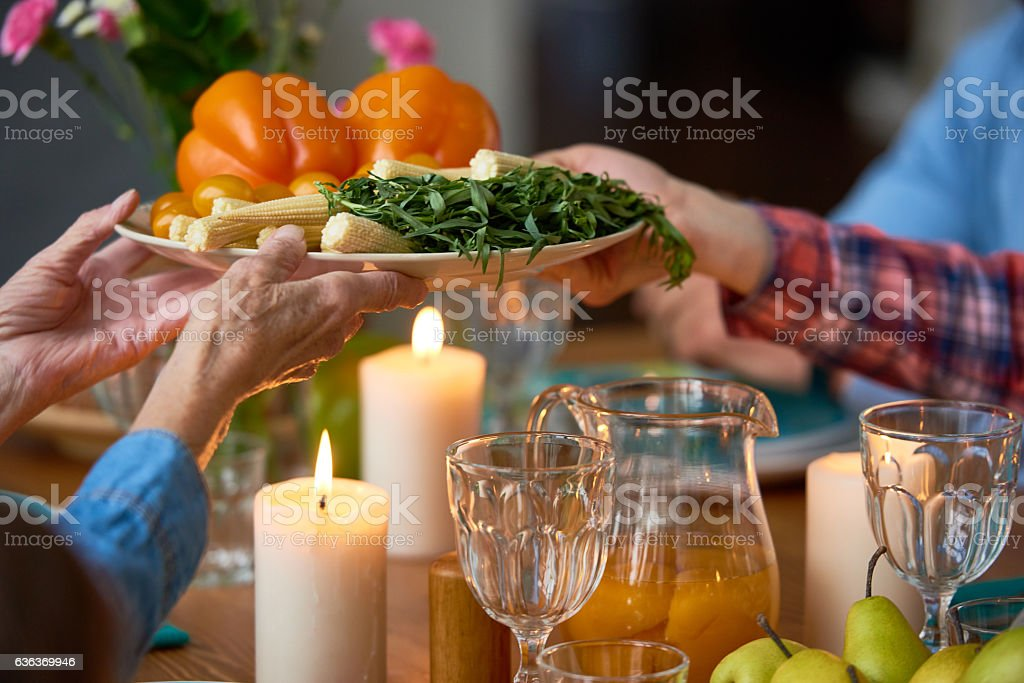 Senior woman passing vegetable plate to daughter stock photo