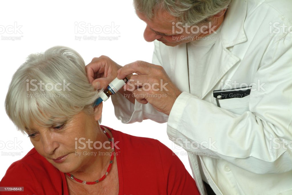 Senior woman patient and Doctor applying eardrops royalty-free stock photo