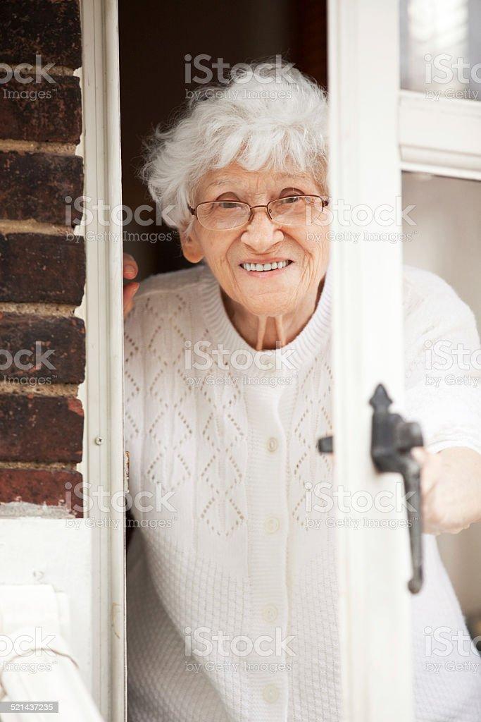 Senior Woman Peeking Though Door stock photo