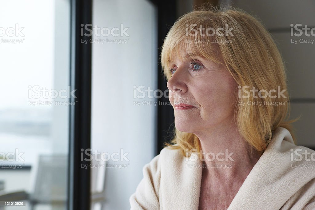 Senior Woman Pensively Looking Out a Window royalty-free stock photo