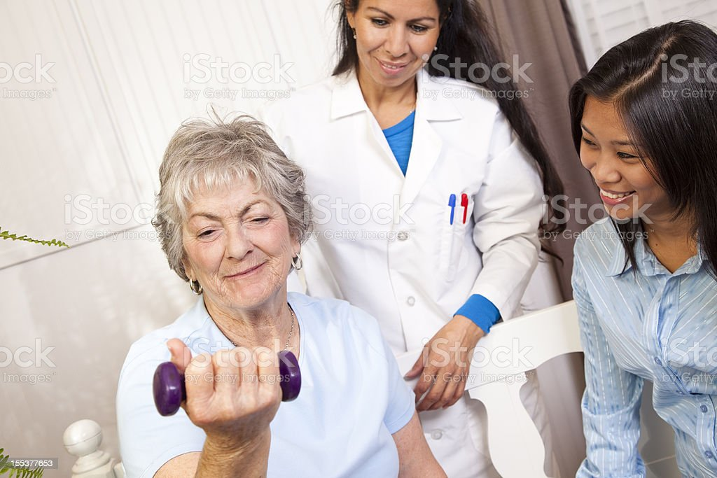 Senior woman. Physical therapy with doctor, family member. Lifting weights. royalty-free stock photo