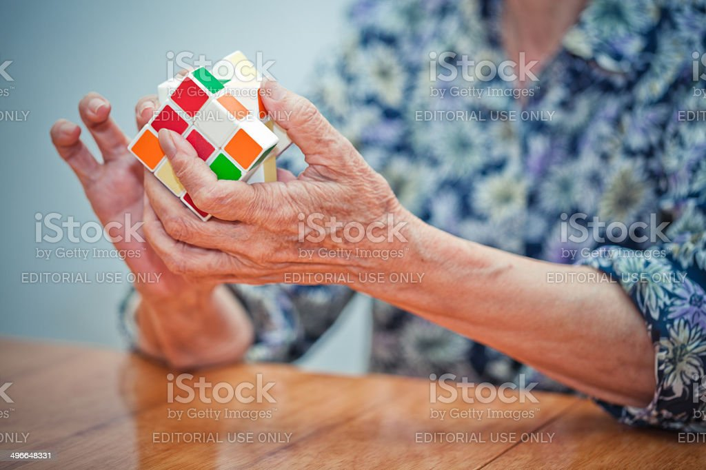 Senior woman playing a cube game stock photo