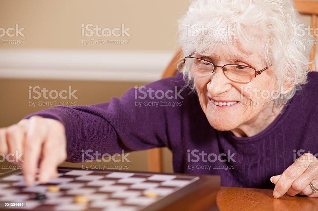 Senior Woman Playing Checkers stock photo