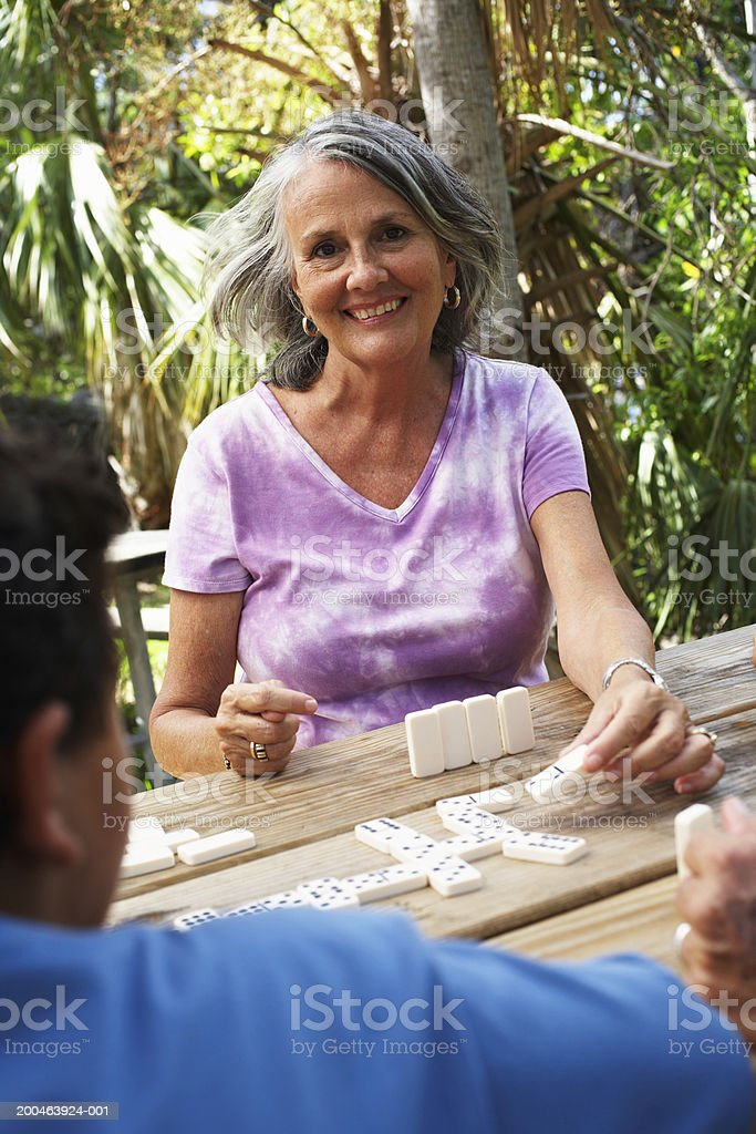 Senior woman playing dominoes at garden table, smiling, portrait royalty-free stock photo