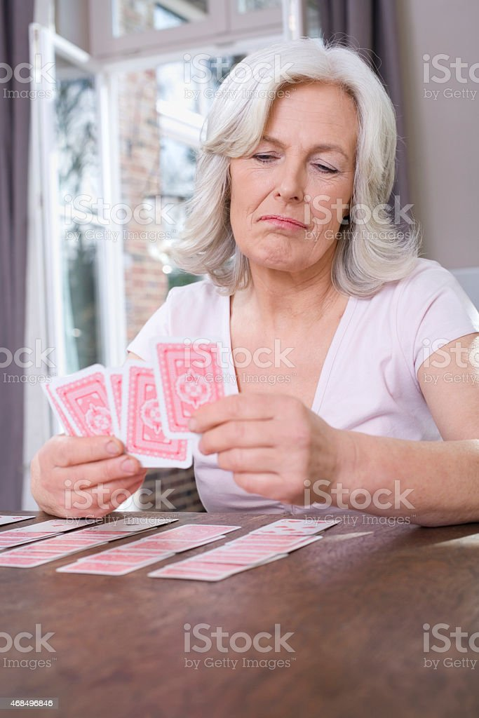 Senior woman playing Solitaire at home stock photo