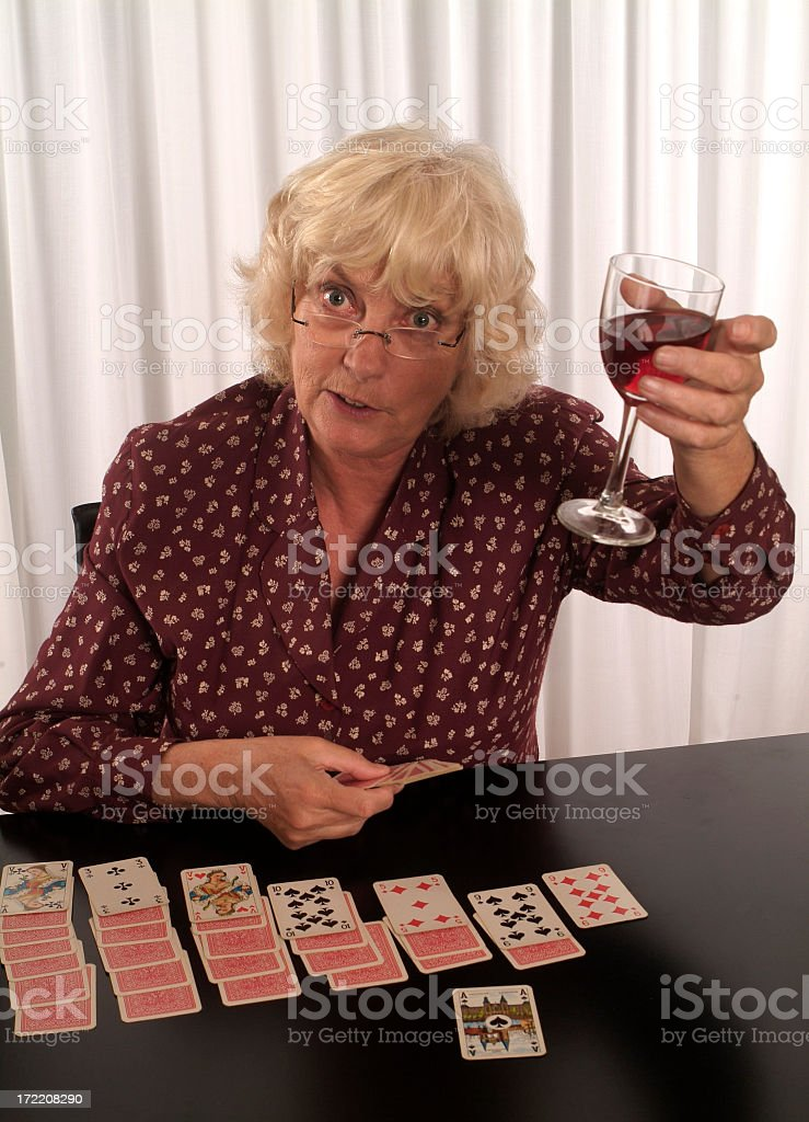 Senior woman playing solitaire with glass of wine stock photo
