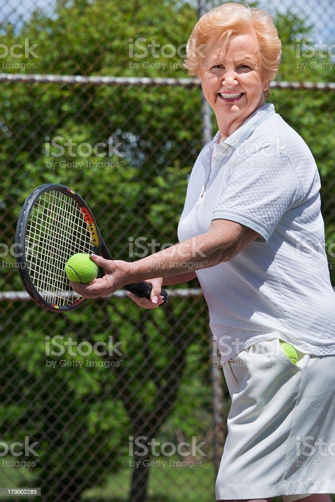 Senior woman playing tennis royalty-free stock photo