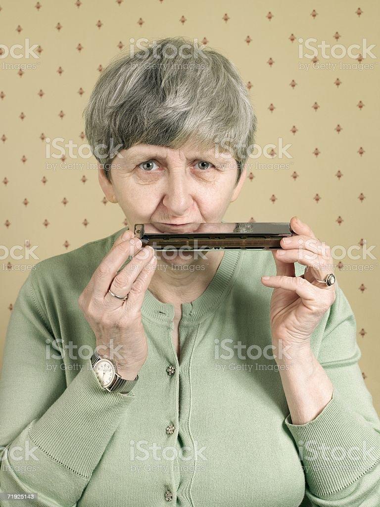 Senior woman playing the harmonica royalty-free stock photo