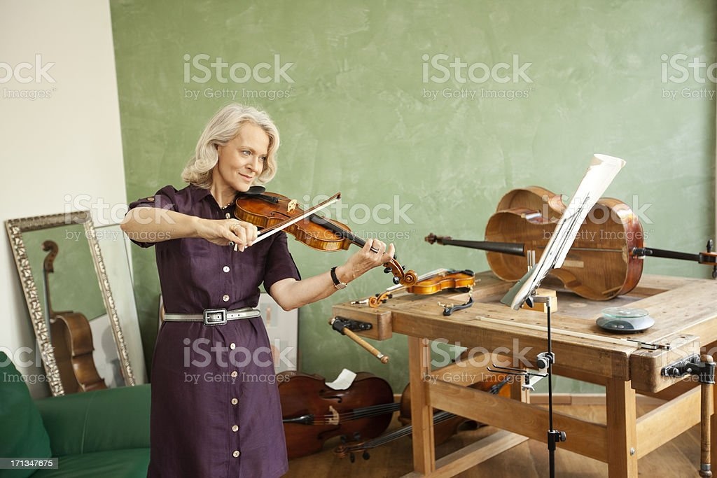 Senior woman playing violin stock photo