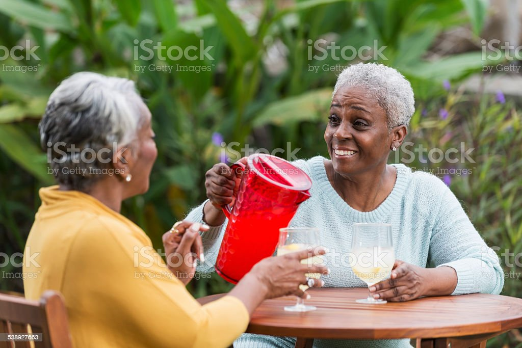 Senior woman pouring drink for a friend stock photo