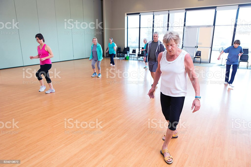 Senior woman practices dance in studio of senior center stock photo