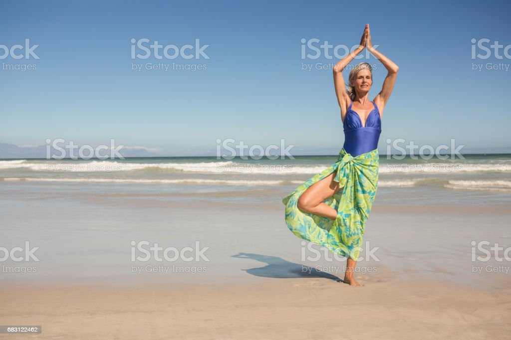 Senior woman practising yoga while standing against clear sky stock photo