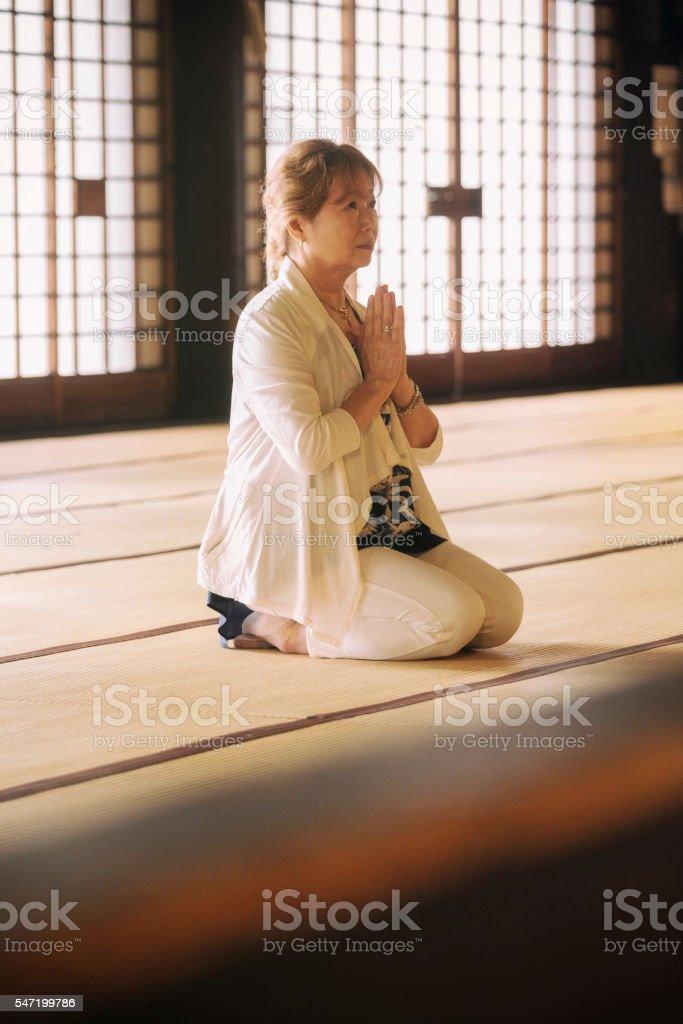 Senior Woman Praying in Buddhist Temple stock photo