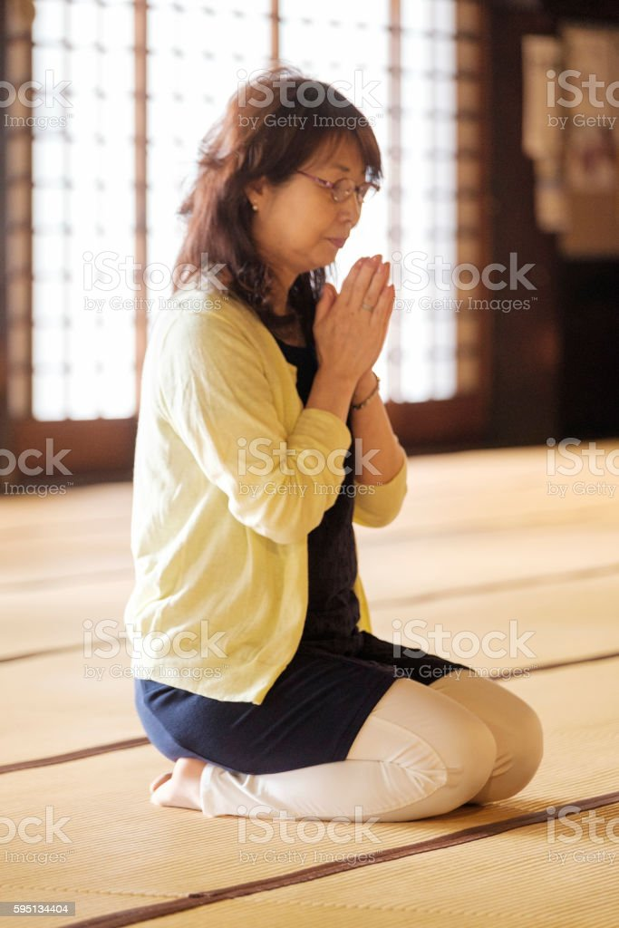 Senior Woman Praying in Buddhist Temple stock photo