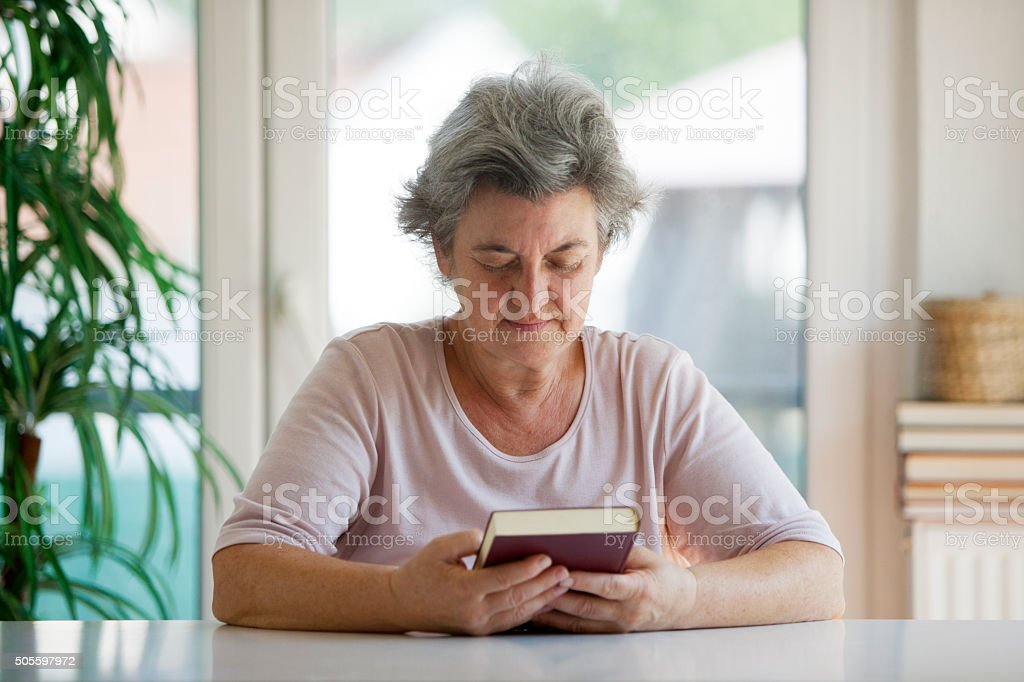 senior woman praying stock photo