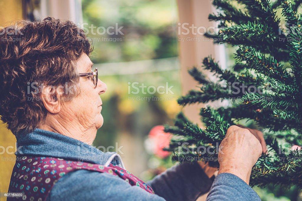 Senior Woman Preparing Christmas Tree on Balcony, Slovenia, Europe stock photo
