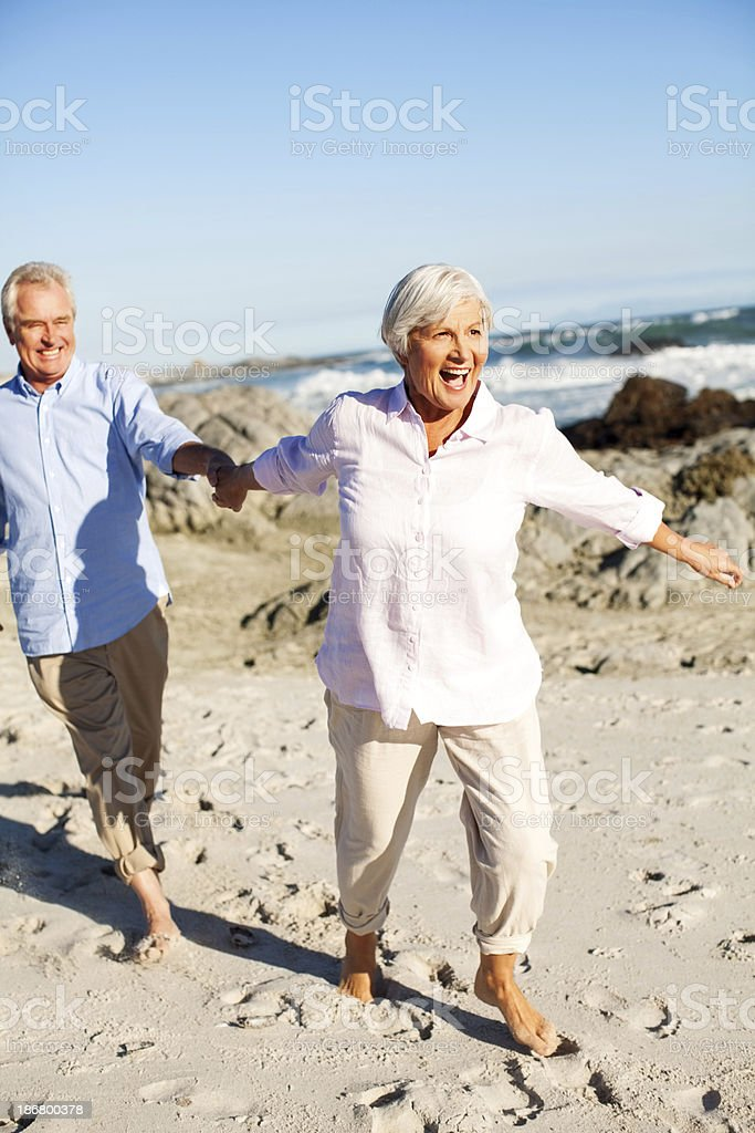 Senior Woman Pulling Man's Hand While Walking On Beach royalty-free stock photo