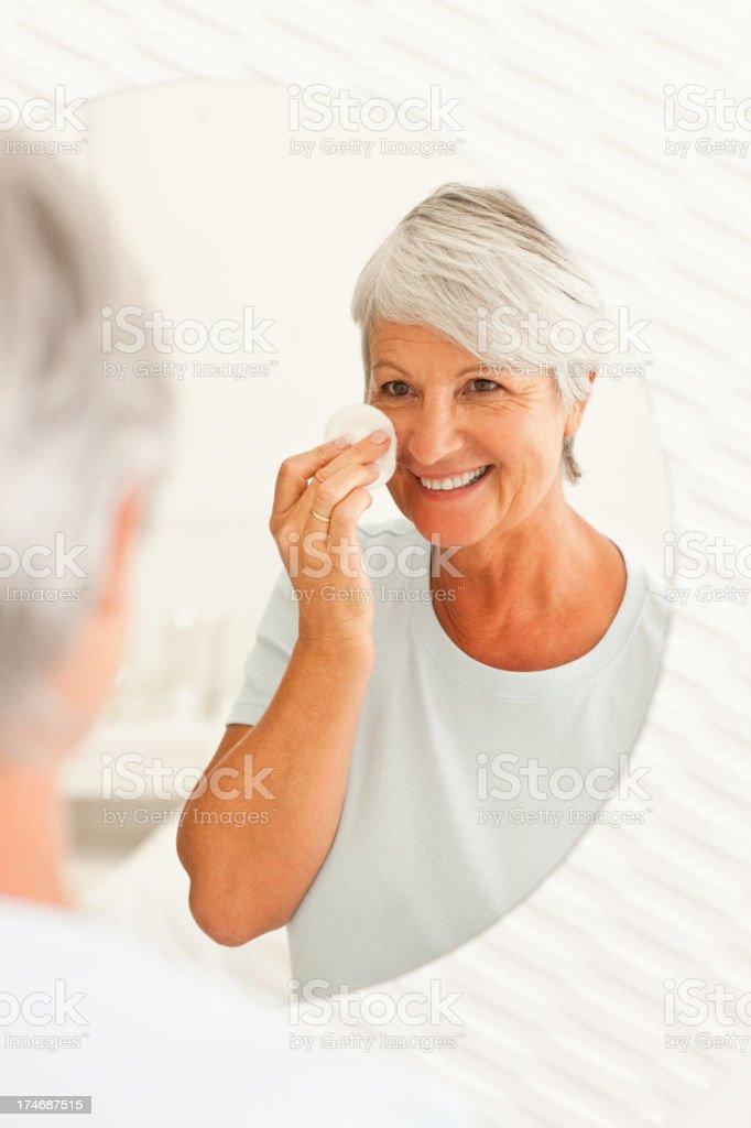 Senior woman putting on makeup royalty-free stock photo