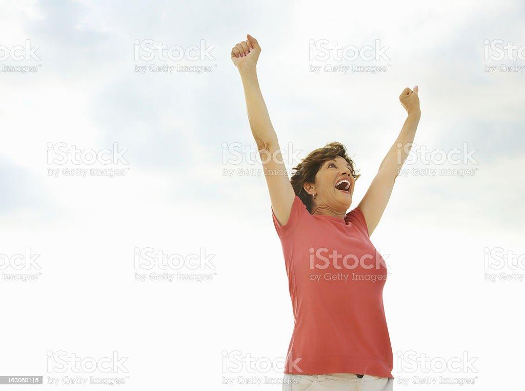 Senior woman raising arms against the sky in joy royalty-free stock photo