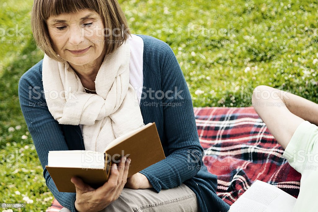 Senior Woman Reading a Book at the Park - Bleached royalty-free stock photo