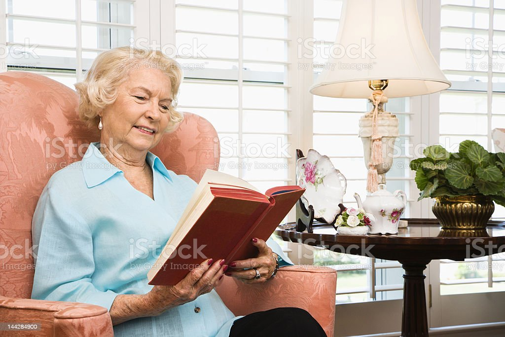 Senior woman reading a book on an arm chair royalty-free stock photo