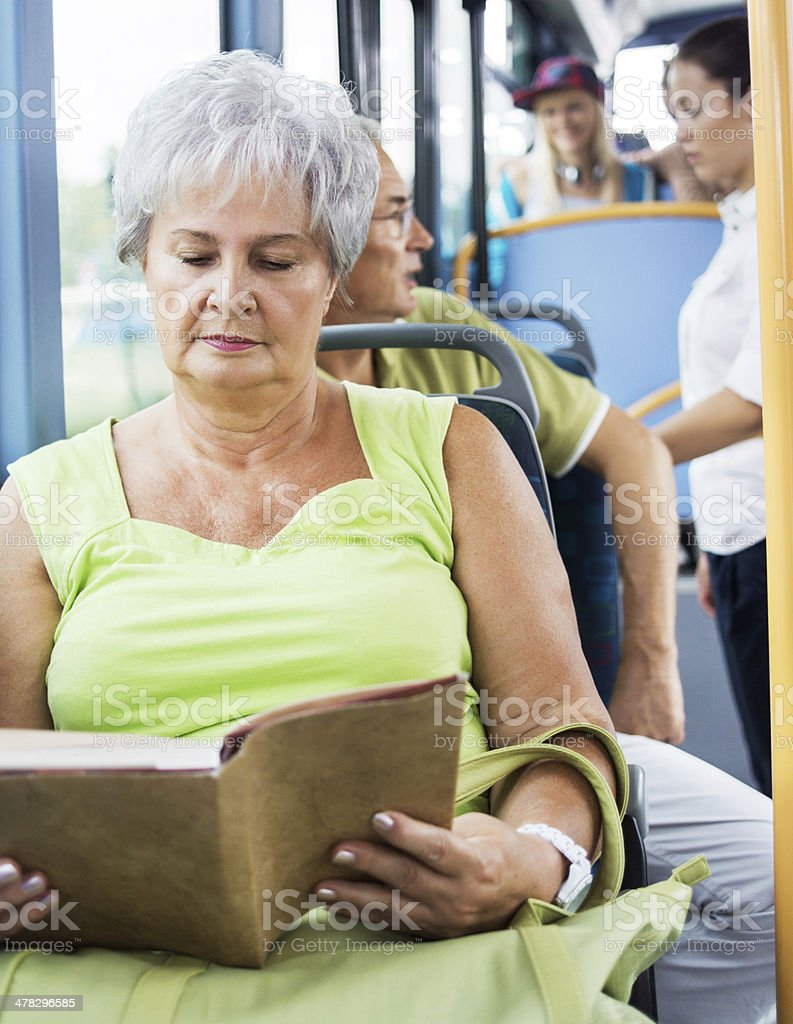 Senior woman reading a book while commuting by bus. royalty-free stock photo
