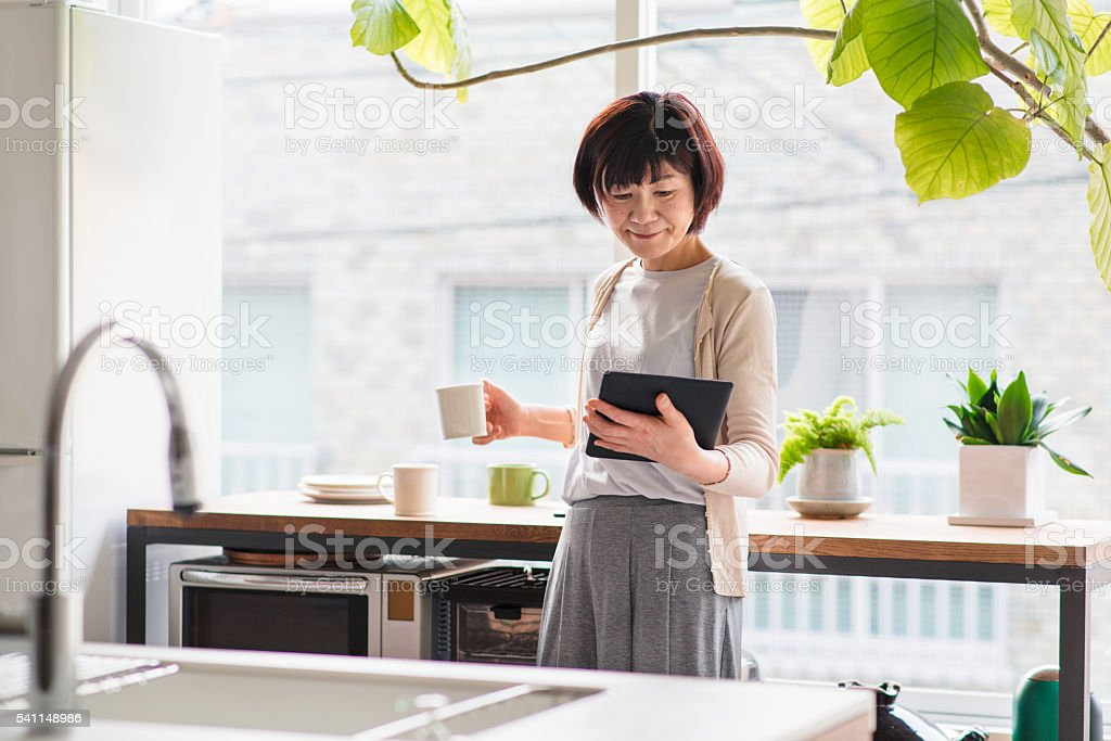 Senior woman reading a digital tablet stock photo