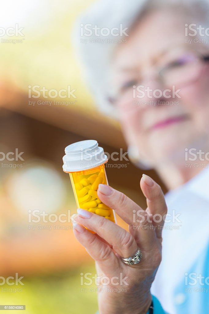 Senior woman reading a prescription medication label stock photo