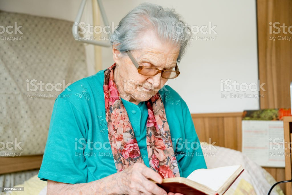Senior Woman Reading Bible In Her Bedroom At The Nursery Home stock photo