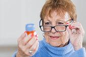 Senior woman reading directions on prescription bottle