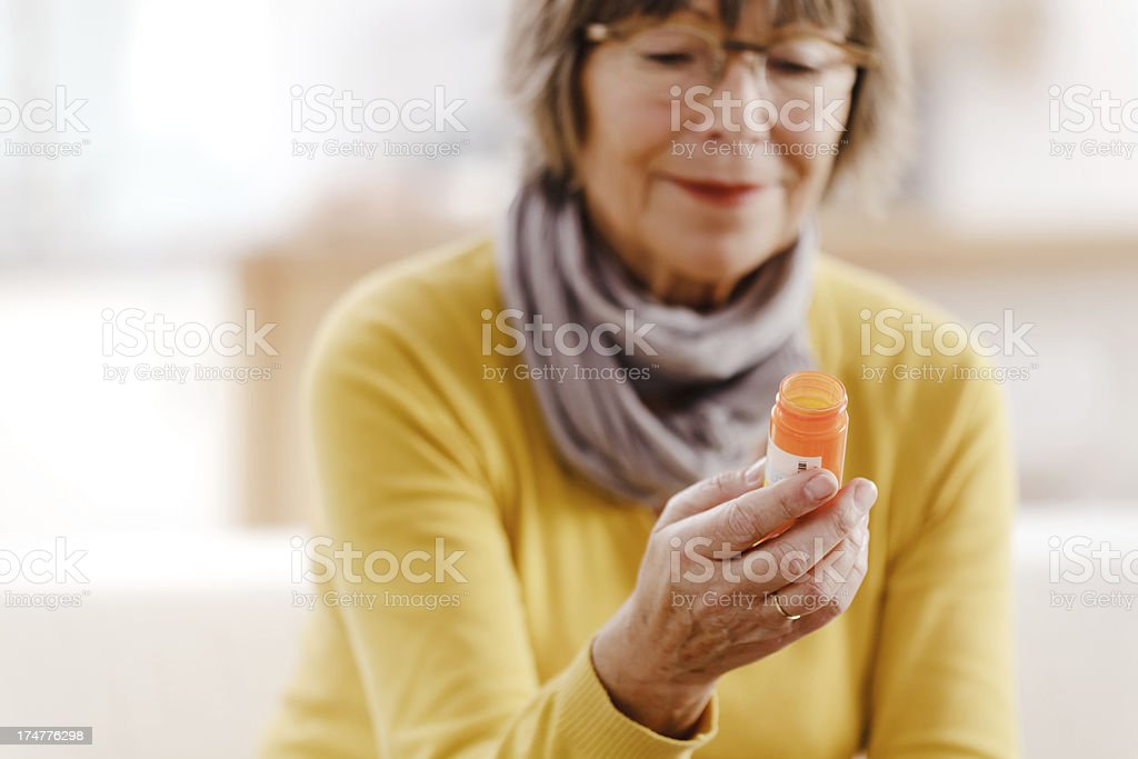 Senior woman reading label on medicine stock photo