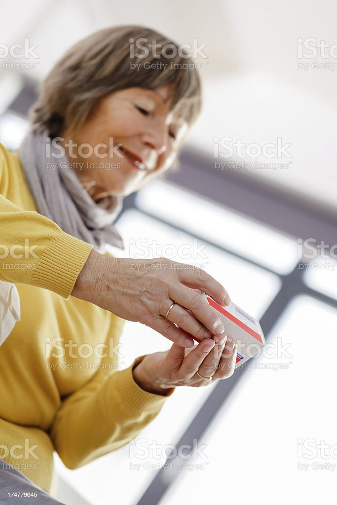 Senior woman reading label on medicine royalty-free stock photo