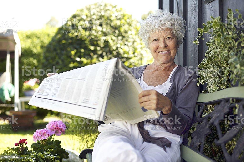 Senior woman reading newspaper in backyard garden stock photo