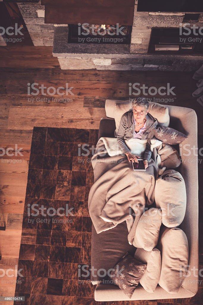 Senior Woman Reading on Sofa stock photo