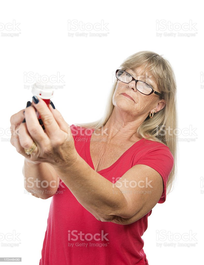 Senior woman reading pill bottle. stock photo