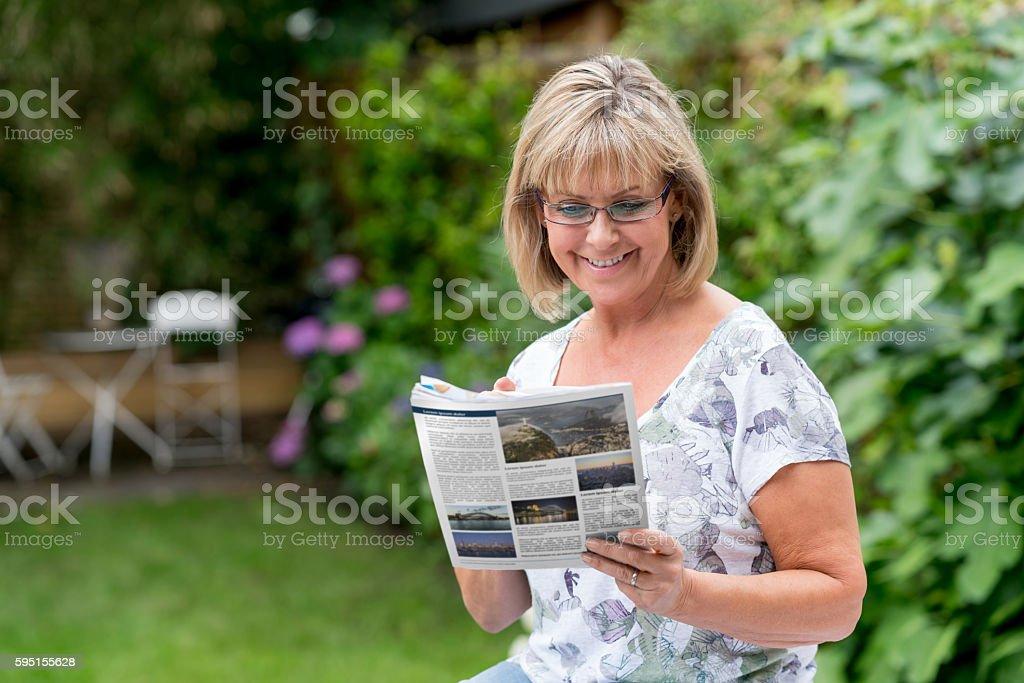 Senior woman reading the newspaper stock photo