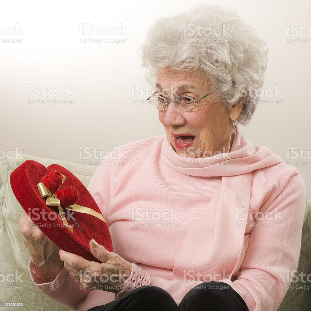 senior woman receives a heart shaped Valentine's Day gift stock photo