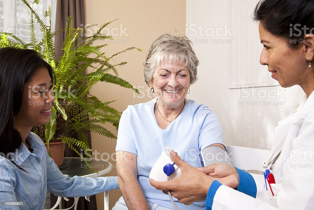 Senior woman receiving blood pressure check in doctor's office royalty-free stock photo