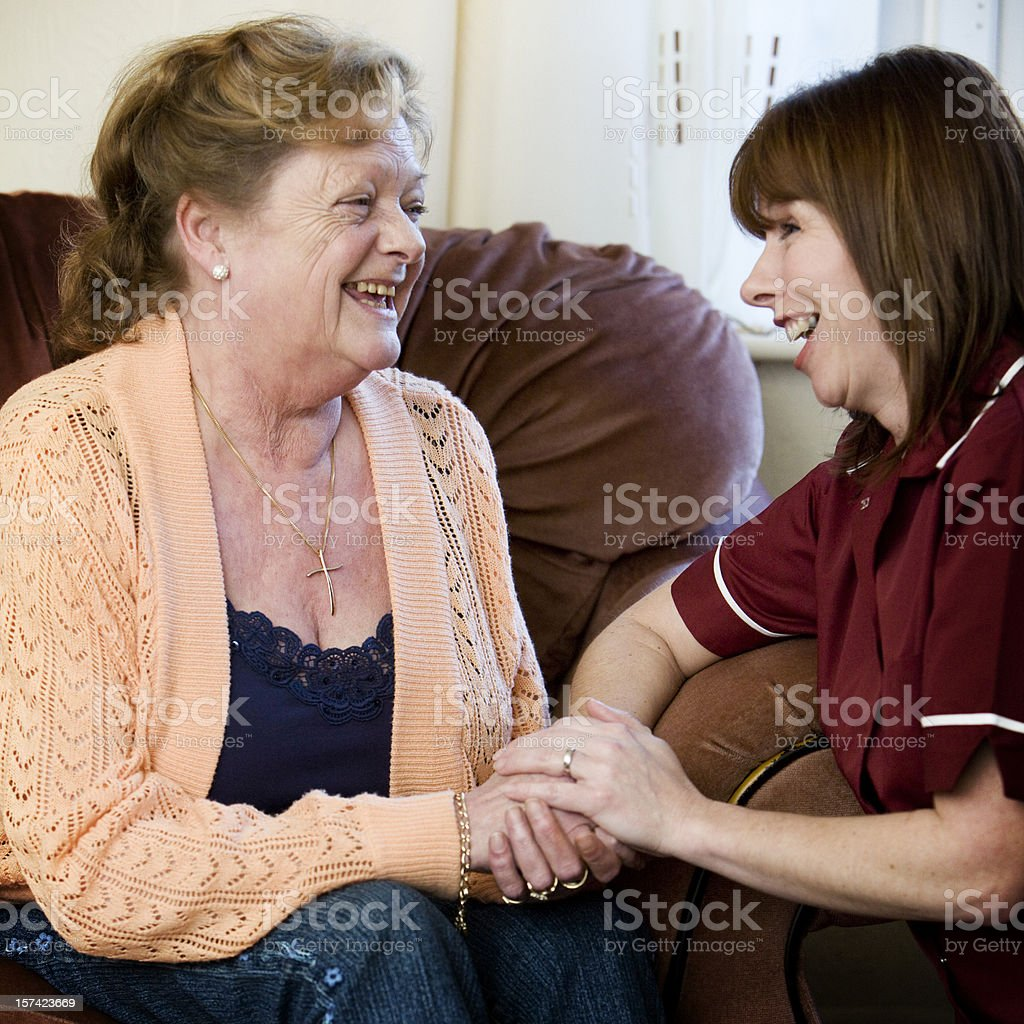 Senior woman receiving home help from a care nurse royalty-free stock photo