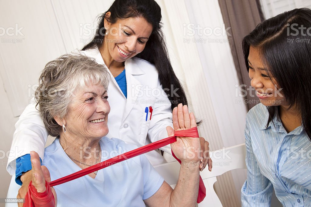 Senior woman receiving home physical therapy. Therapist, doctor. Resistance band. royalty-free stock photo