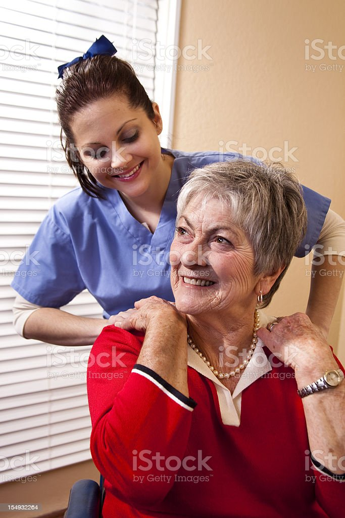 Senior woman receiving home therapy on her shoulders royalty-free stock photo