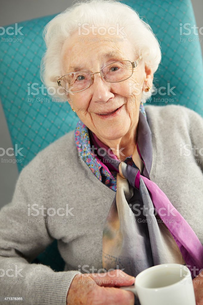 Senior Woman Relaxing In Chair With Hot Drink stock photo