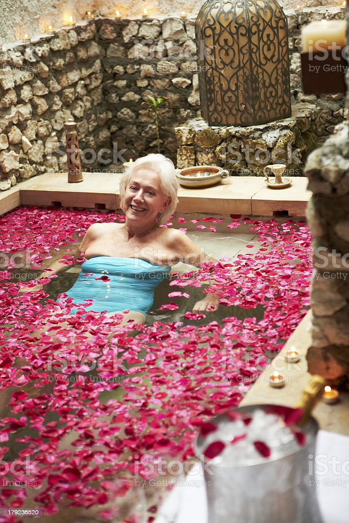 Senior Woman Relaxing In Flower Petal Covered Pool At Spa royalty-free stock photo