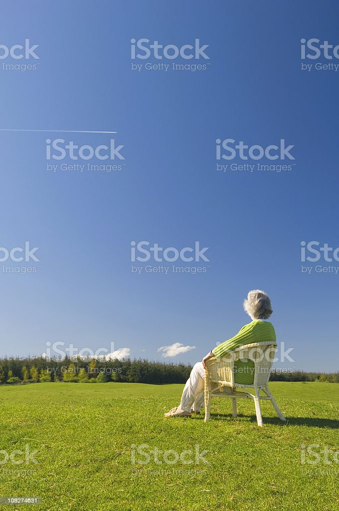 Senior woman relaxing outdoors stock photo