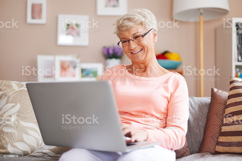 Senior woman relaxing with laptop on sofa stock photo