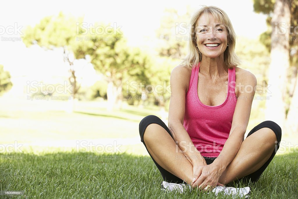 Senior Woman Resting After Exercising In Park stock photo